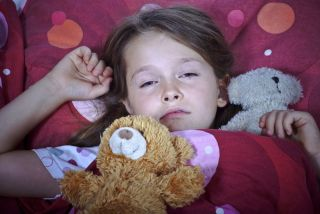 Sleepy young girl in bed holding a teddy bear.