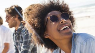 Eye health tips: A smiling woman wears sunglasses to protect her eyes in blazing sunshine