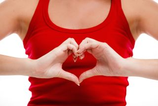 A woman places her hands in the shape of a heart over her chest.