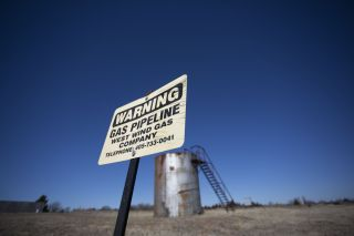 Wastewater injection related to oil and gas drilling can trigger earthquakes in Oklahoma. Here, a sign showing a gas line in front of a storage tank in McLoud, Oklahoma.