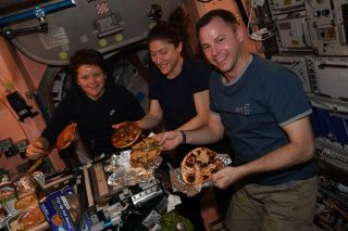 NASA astronauts Anne McClain, Christina Koch and Nick Hague show off their homemade pizza dinner on April 5, 2019.