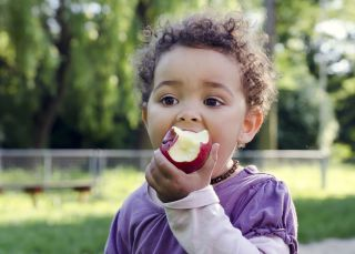 Young girl eating an apple.