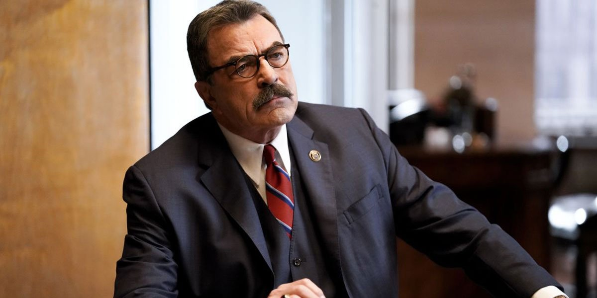 Tom Selleck looking serious and sitting at a desk.