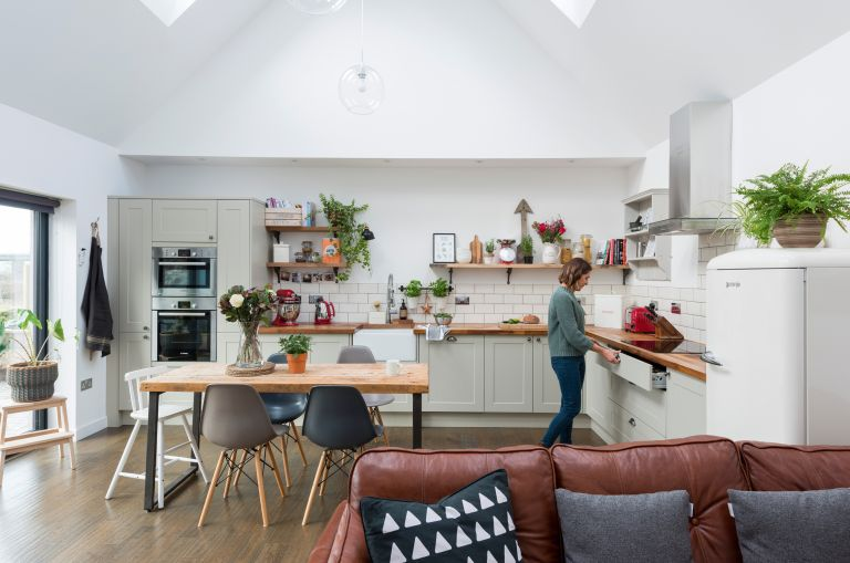 A double-height kitchen diner extension with rooflights, built-in kitchen units and a family dining table