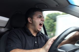 Angry man driving a car without a seatbelt.