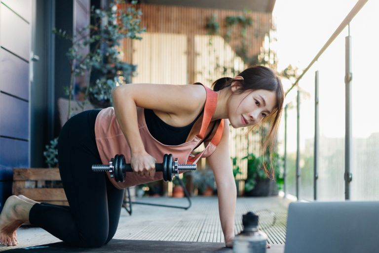 best dumbbells for women - young Asian woman exercising with dumbbells outside