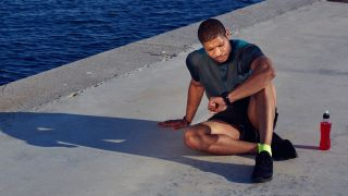 Man in workout clothing resting and checking his running watch