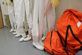 Pressurized suits for handling dangerous pathogens