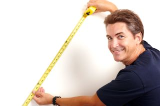 a man measuring a wall with measuring tape