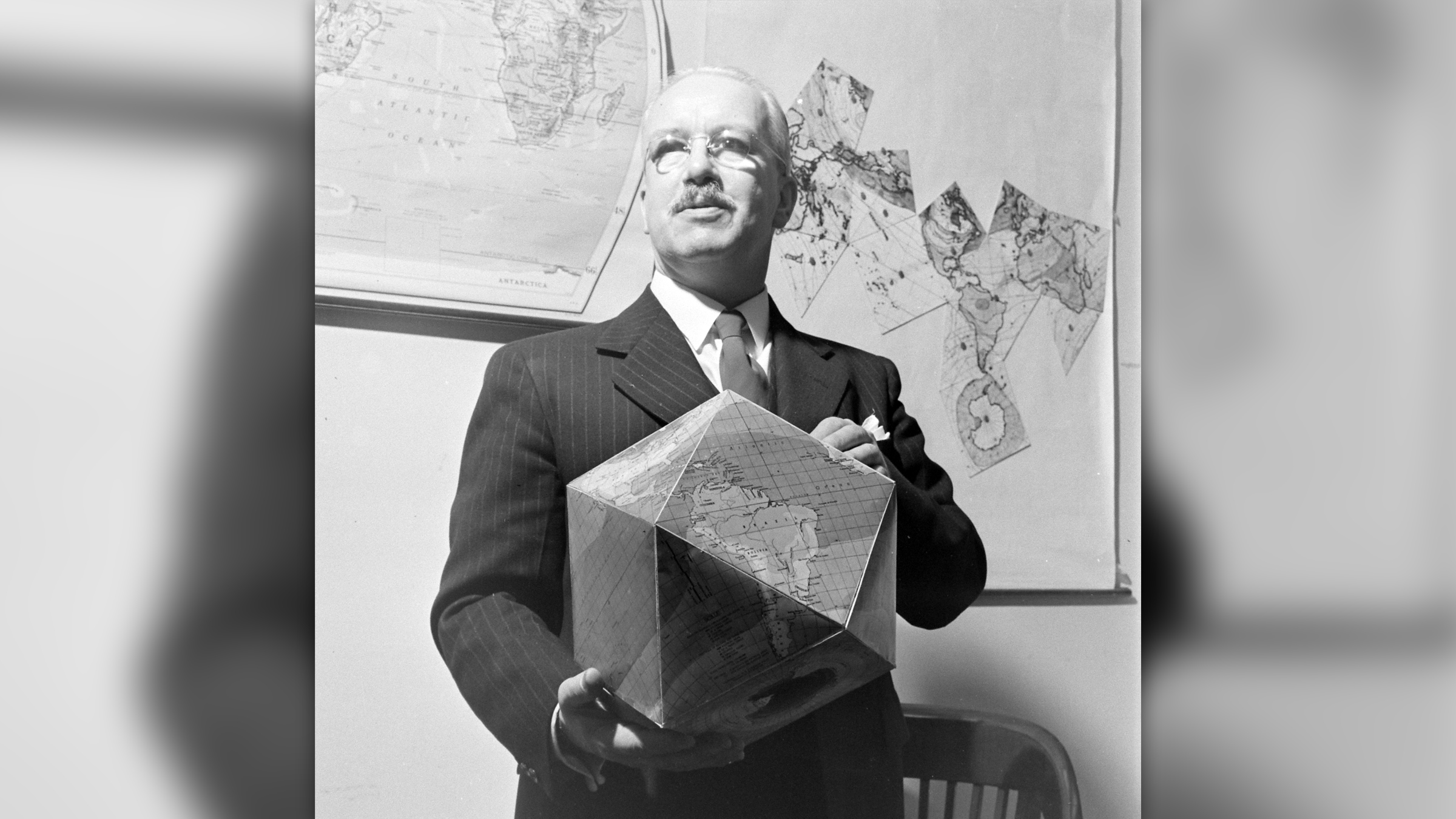 Richard Buckminster Fuller holds his assembled polyhedral globe. Note the flat map on the wall in the background.