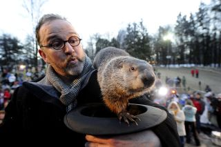 Groundhog handler Ben Hughes watches Punxsutawney Phil after he did not see his shadow, suggesting an early spring during Groundhog Day festivities on Feb. 2, 2011, in Punxsutawney, Pennsylvania.