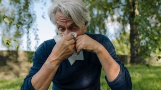 What causes allergies? Image shows man blowing nose