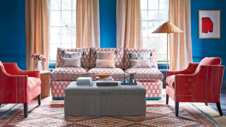 A blue living room with red armchairs, red and white sofa and wicker lamp