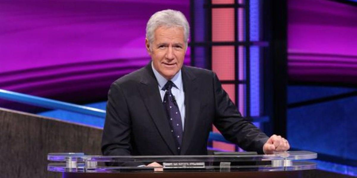 Alex Trebek smiling at his desk on the set of Jeopardy!