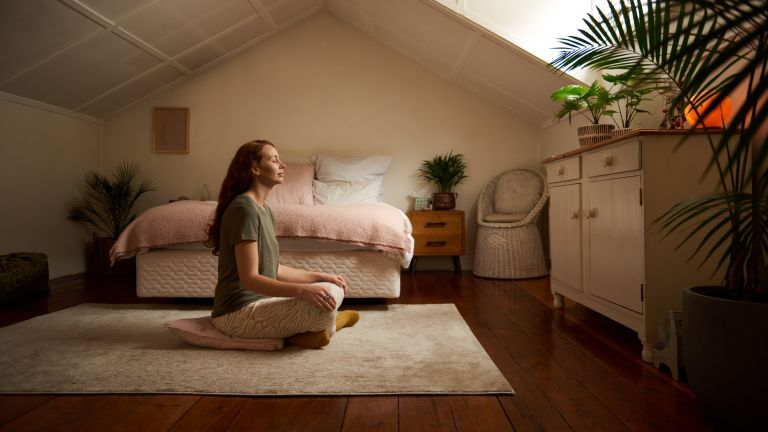 Woman doing yoga meditation in a bedroom