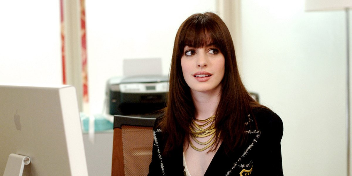 Andy (Anne Hathaway) sits at a desk in 'The Devil Wears Prada'