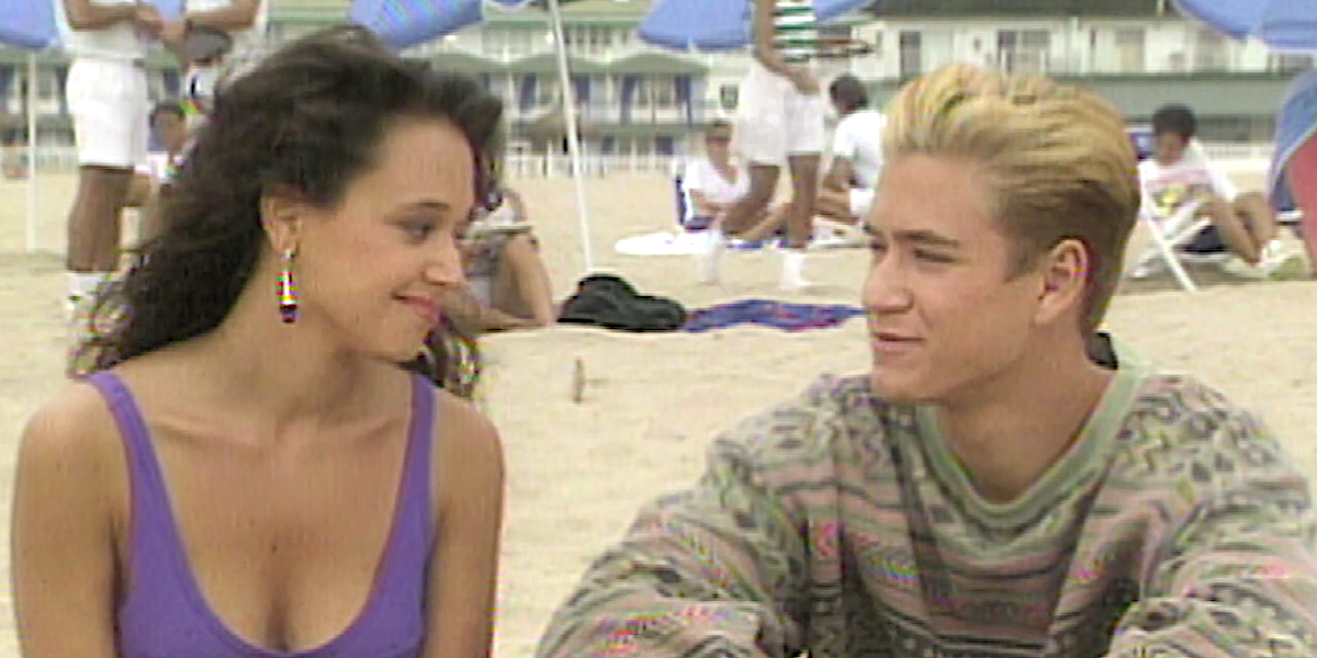 Saved by the Bell Leah Remini as Stacey Carosi looks at Zack Morris on the beach.