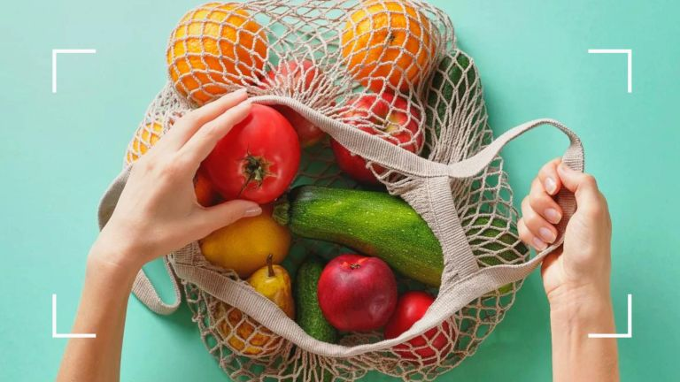 woman reaching into a bag of fruit and vegetables