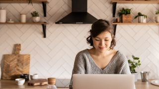 Best free blogging platforms: Woman using laptop in kitchen