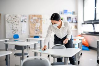 A teacher wearing a mask while cleaning a classroom.