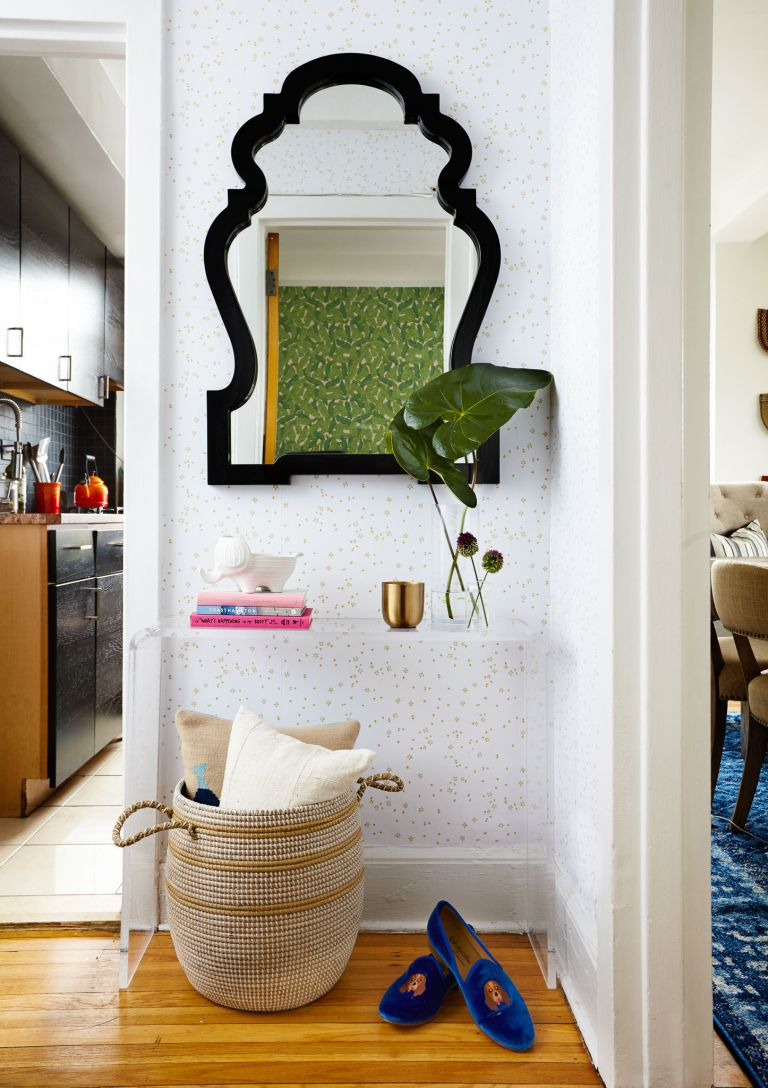 Delicately wallpapered hallway with contemporary mirror and floating shelf