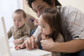 Asian father with two children at laptop computer