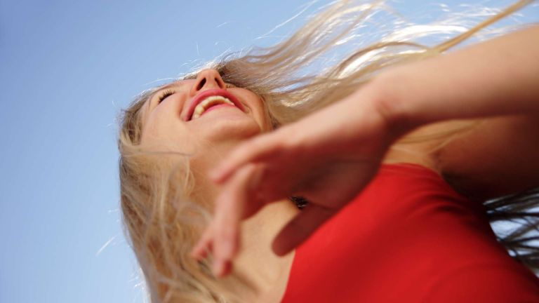 Woman with shiny hair smiling in front of blue sky