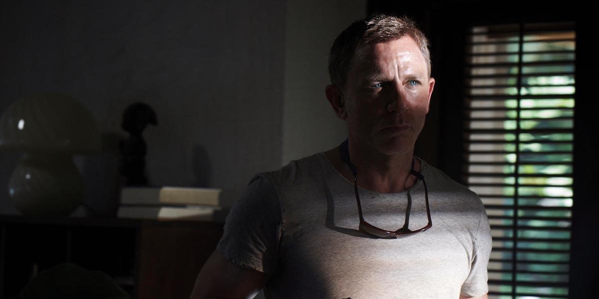 James Bond (Daniel Craig) peers through a window in 'No Time To Die'