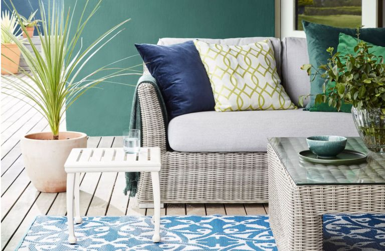 An example of patio ideas and designs showing wicker furniture, potted plants and an outdoor rug