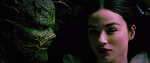 A slimy green monster known as Swamp Thing looks longingly at a beautiful sultry woman