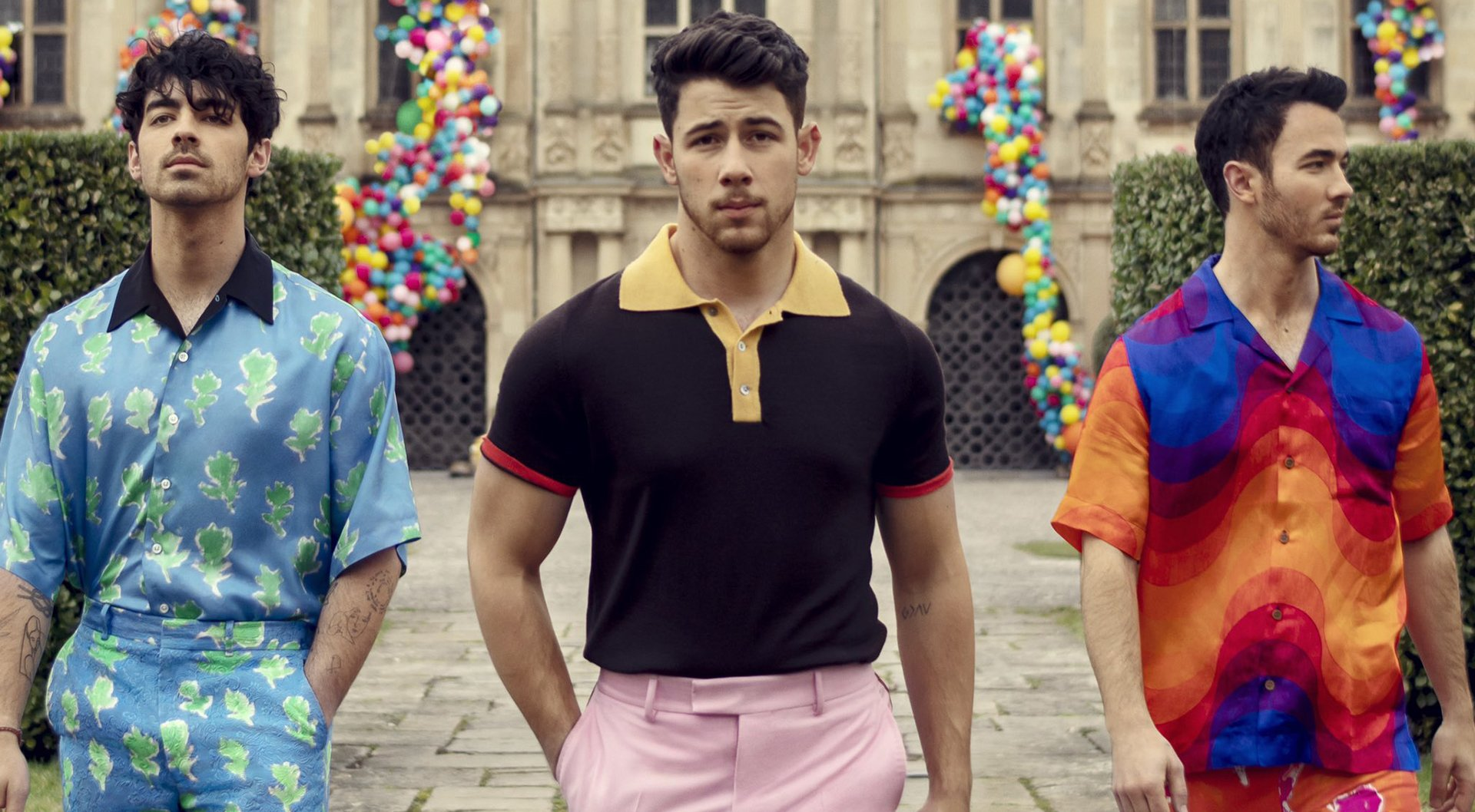 The Jonas Brothers walking past some hedges in the Sucker music video.
