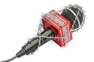 A microphone wrapped in barbed wire.