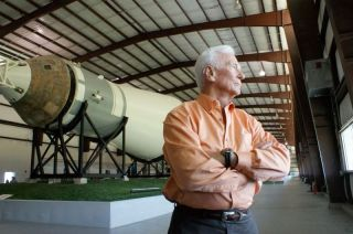 Eugene Cernan, in an orange shirt, crosses his arms in front of part of a spaceship