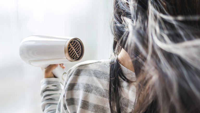 Best hair dryer: blow drying long dark hair shot from behind