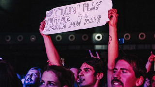 A picture of a Bullet For My Valentine fan holding up a sign asking to play live with the band in Austria