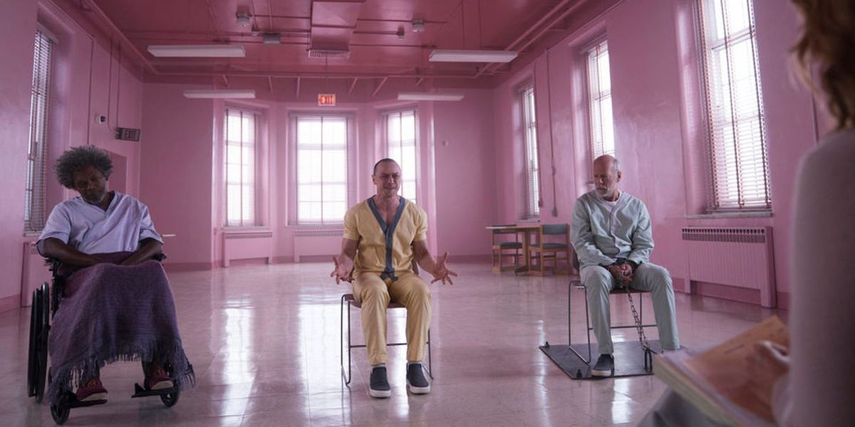 Elijah Price, Kevin Crumb and David Dunn sit in chairs in a pink room in 'Glass'