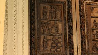 """A wooden door at the Santa Sabina Church in Rome shows Jesus with a """"wand"""" performing miracles: (top to bottom) Jesus raising Lazarus; Jesus multiplying loaves and fish; Jesus turning water into wine."""