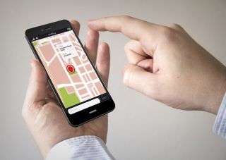 Hand checking location data on a smartphone.