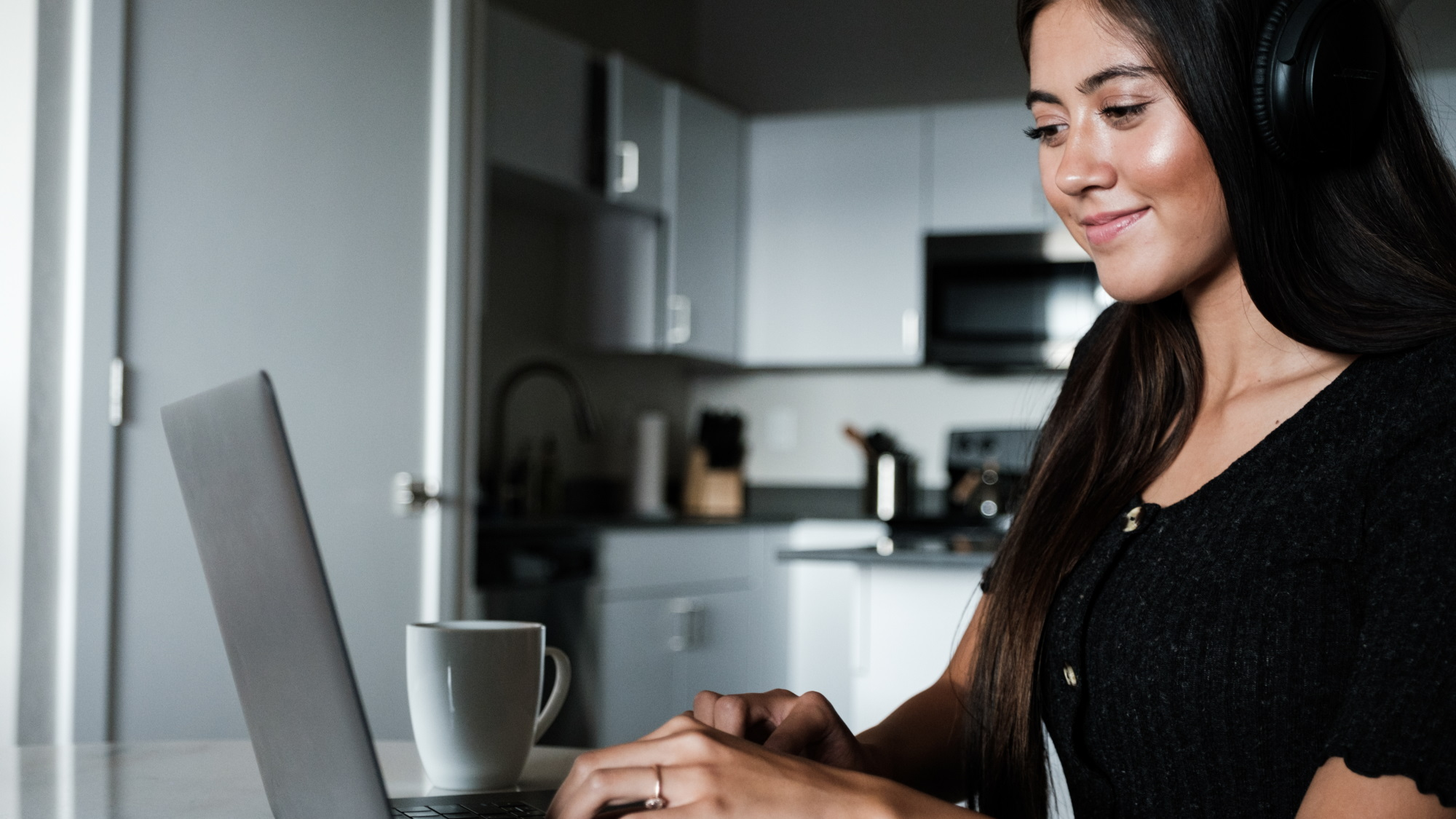 Woman coding on a laptop in her kitchen