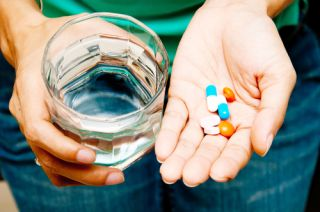 A woman holds a handful of pills and a glass of water.