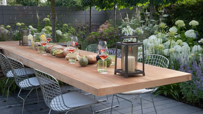 outdoor dining space in an urban garden surrounded by a mix of the best plants for small gardens