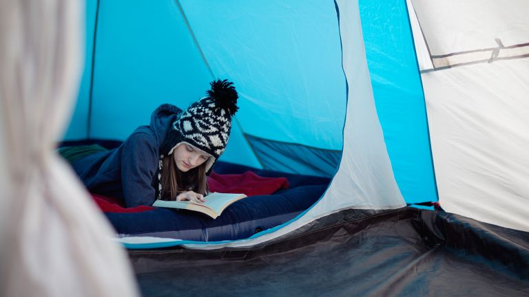 best camping bed: teenager reading on an inflatable campbed
