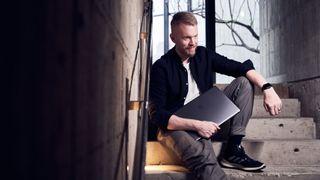 Man sitting on steps holding a laptop
