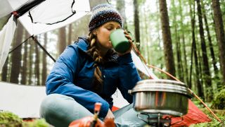Best camping mugs: A woman drinking from a mug while camping