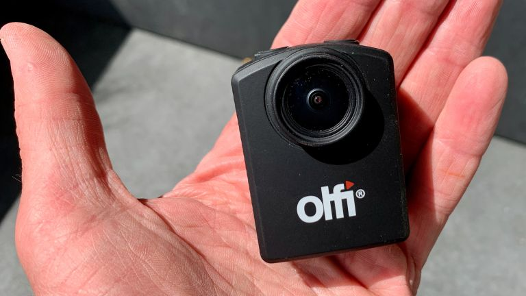Olfi one.five Black action camera on someone's palm