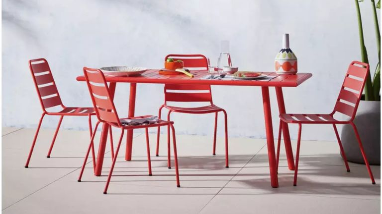 A red metal outdoor dining table and chairs