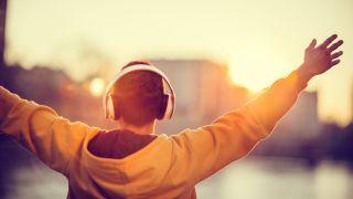 Mies levittää kätensä kohti aurinkoa kuulokkeet päässä