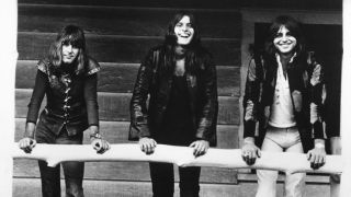 Keith Emerson, Carl Palmer and Greg Lake standing on the porch of a wooden cabin