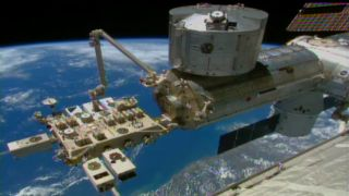 This video frame shows a robotic arm on the International Space Station, called the Japanese Experiment Module Remote Manipulator System, installing NASA's Cloud-Aerosol Transport System (CATS) on the orbiting lab's Japanese Experiment Module on Jan. 22,