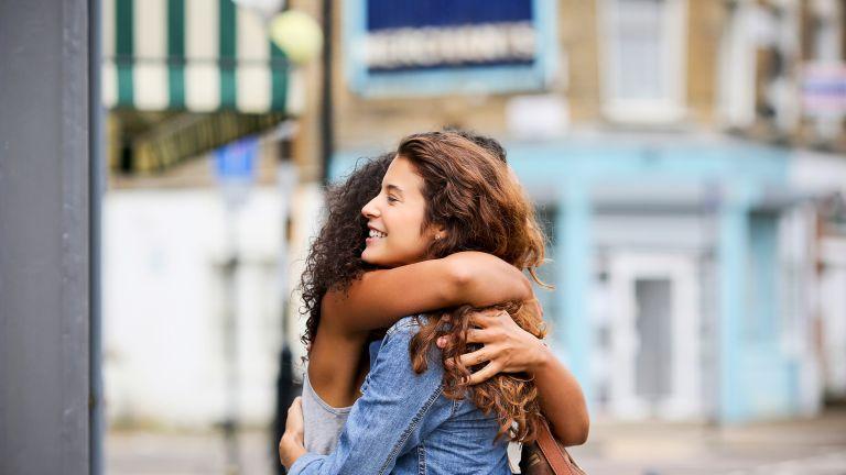 two women hugging outdoors